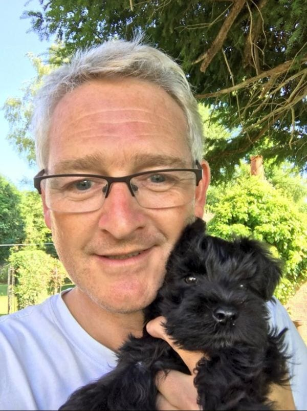 man and little black dog
