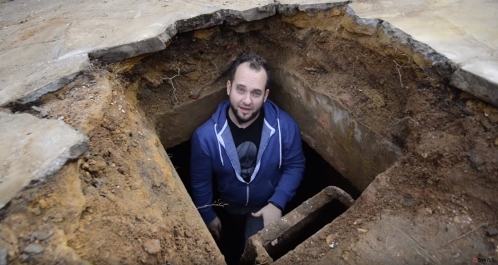simon marks stands inside giant hole