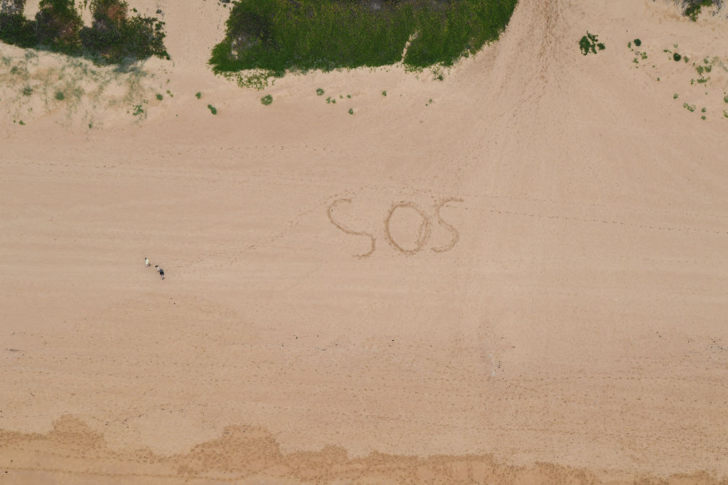SYDNEY, AUSTRALIA - DECEMBER 21: An aerial view of 'SOS' written in the sand at Curl Curl beach on December 21, 2020 in Sydney, Australia