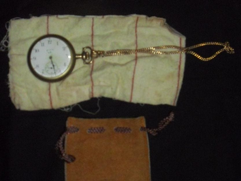 Pocket watch, cloth, and leather pouch