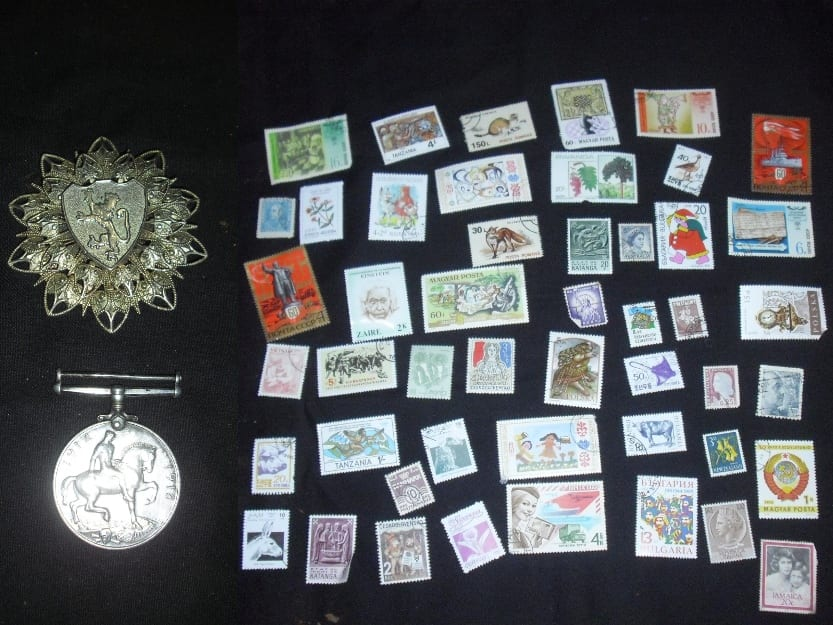 Two war medals next to stamp collection