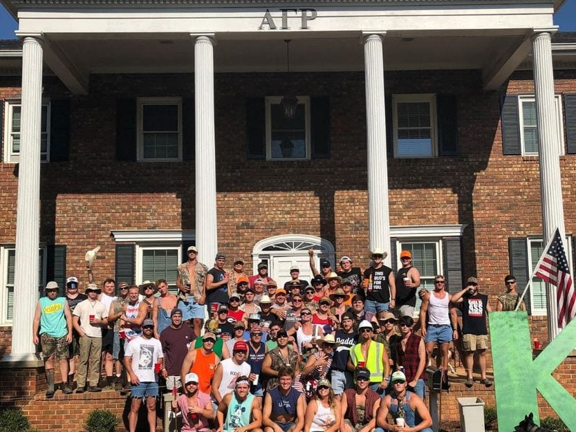 fraternity members in front of house