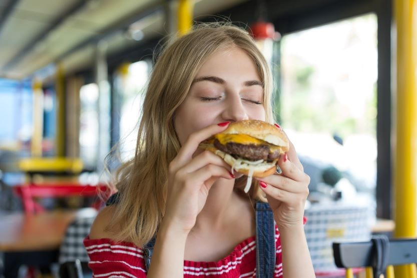 Girl biting into cheeseburger everyday items