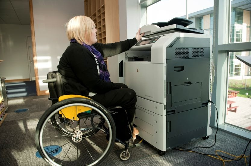 Woman in wheelchair using copy machine everyday items
