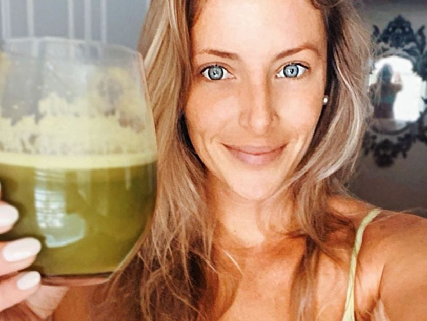 Girl holding glass of green juice